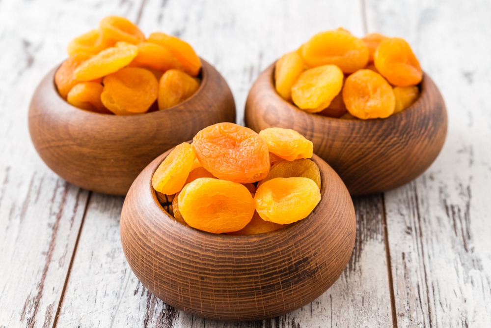 Dried apricots in wooden bowl on wooden white table